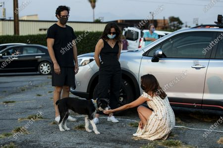 Aubrey Plaza (R) interacts with a dog as she arrives to attend to the ArcLight Drive-In special screening of 'The Little Hours' at the Vineland Drive-In in the City of Industry, east of Los Angeles, California, USA, 19 August 2020.