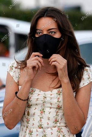 """Aubrey Plaza, a cast member in """"The Little Hours,"""" adjusts her mask before a drive-in screening of the film presented by ArcLight Cinemas at the Vineland Drive-In theater, in Industry, Calif"""