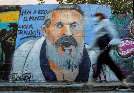 A woman walks past a graffiti picturing Spanish singer Miguel Bose and reading 'Hello Everyone. Hello Dr. Nick' on a street in Valencia, eastern Spain, 20 August 2020. The singer made some controversial statements on coronavirus and the compulsory use of face masks. Dr. Nick is one of The Simpsons character known for his crazy diagnosis.