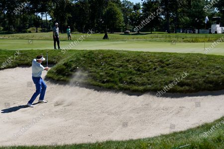 Ian Poulter hits from a bunker onto the 14th green in the first round of the Northern Trust golf tournament at TPC Boston, in Norton, Mass