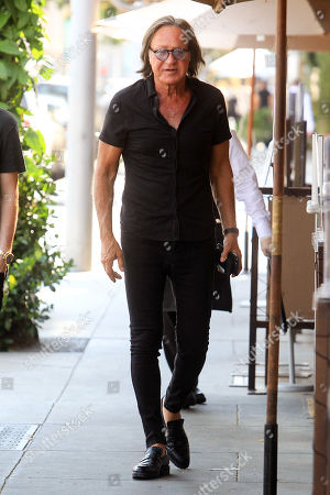 Stock Photo of Mohamed Hadid down the street past a restaurant