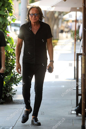 Mohamed Hadid down the street past a restaurant