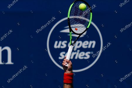 Serbia's Laslo Djere serves to Marcos Giron during the qualifying round at the Western & Southern Open tennis tournament, in New York