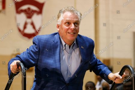 Former Virginia Gov. Terry McAuliffe walks up to the stage as he prepares to introduce Democratic presidential candidate former Vice President Joe Biden, during a campaign rally in Norfolk, Va. McAuliffe has filed paperwork to run for his old job next year but says he's still hasn't made an official decision yet