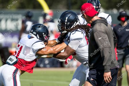 Houston Texans linebacker Dylan Cole (51) hits linebacker Peter Kalambayi (58) as they run a drill during NFL football training camp, in Houston