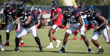 Houston Texans quarterback Deshaun Watson (4) takes a snap as he runs a play behind running back David Johnson (31), guard Senio Kelemete (64) tackle Laremy Tunsil (78) and tight end Jordan Akins (88) during an NFL training camp football practice, in Houston