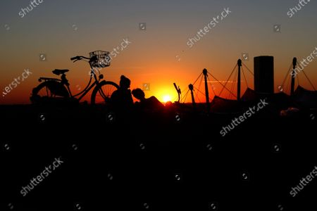 Stock Image of Young people enjoy the sun set at the Olympic park in Munich, Germany, Thursday, Aug.20, 2020