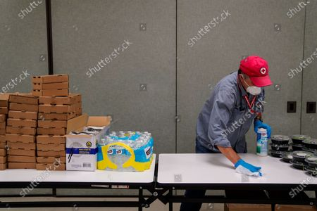 Red Cross volunteer John Williams, 72, of Benicia wipes down the surface of a table where he is handing out salads and pizzas to those displaced by the Hennessy Fire at the Vacavile Community Center on Wednesday, Aug. 19, 2020 in Vacaville, CA. (Kent Nishimura / Los Angeles Times)