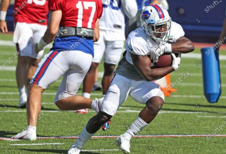 Buffalo Bills running back Devin Singletary (26) protects the ball as he carries it after taking the handoff from quarterback Josh Allen (17) during an NFL football training camp in Orchard Park, N.Y