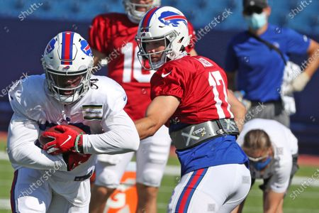 Buffalo Bills quarterback Josh Allen, right, hands off the ball to Bills running back Zack Moss during an NFL football training camp in Orchard Park, N.Y