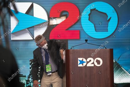 August 20, 2020; Milwaukee, WI, USA; Douglas Fogel cleans the podium after Democratic National Committee Chairman Tom Perez spoke during the Democratic National Convention at the Wisconsin Center. Mandatory