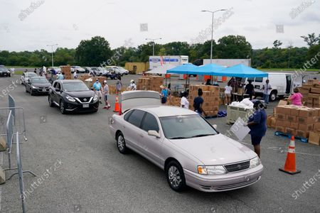 Volunteers with Catholic Charities of the Archdiocese of Washington distribute grocery boxes and ready-to-eat meals to recipients who have been affected by the coronavirus outbreak and economic downturn, in a parking lot outside Robert F. Kennedy Memorial Stadium in Washington