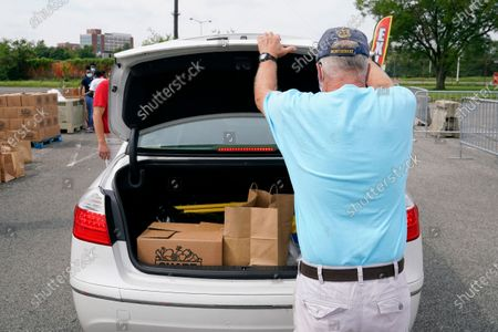 Volunteer with Catholic Charities of the Archdiocese of Washington closes a car trunk after distributing grocery boxes and ready-to-eat meals to recipients who have been affected by the coronavirus outbreak and economic downturn, in a parking lot outside Robert F. Kennedy Memorial Stadium in Washington