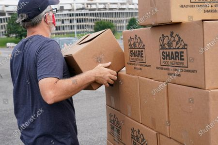 Volunteer with Catholic Charities of the Archdiocese of Washington prepares to distribute a grocery box to recipients who have been affected by the coronavirus outbreak and economic downturn, in a parking lot outside Robert F. Kennedy Memorial Stadium in Washington