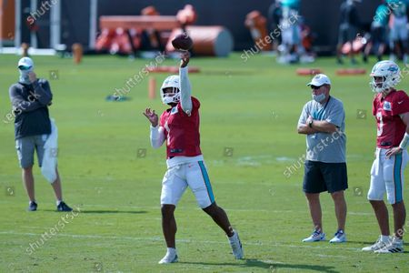 Miami Dolphins quarterback Tua Tagovailoa (1) throws as quarterback Josh Rosen (3) looks on during practice at the NFL football team's training facility, in Davie, Fla. Miami Dolphins quarterback Ryan Fitzpatrick is missing practice for personal reasons. Fitzpatrick's absence left top draft pick Tagovailoa and Rosen to take snaps Friday