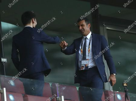 President of Inter Milan, Zhang Kangyang (L), wearing a protective face mask, welcomes former Portuguese soccer player Luis Figo (R) prior to the UEFA Europa League final match between Sevilla FC and Inter Milan in Cologne, Germany 21 August 2020.