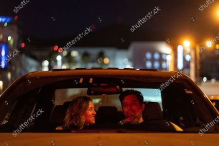 """Jennifer and Matthew Wilson of Downtown Los Angeles in their car, watching National Lampoon's """"Vacation"""" at the Electric Dusk Drive-In atop the old Glendale Sear's parking garage on Saturday, Aug. 8, 2020 in Glendale, CA. Drive-In movies have resurged in popularity amid the coronavirus pandemic shuttering conventional movie theaters and the normal block buster hits that usually are released in the summer months. (Kent Nishimura / Los Angeles Times)"""