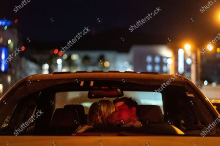 """Jennifer and Matthew Wilson of Downtown Los Angeles share a kiss in their car, while watching National Lampoon's """"Vacation"""" at the Electric Dusk Drive-In atop the old Glendale Sear's parking garage on Saturday, Aug. 8, 2020 in Glendale, CA. Drive-In movies have resurged in popularity amid the coronavirus pandemic shuttering conventional movie theaters and the normal block buster hits that usually are released in the summer months. (Kent Nishimura / Los Angeles Times)"""