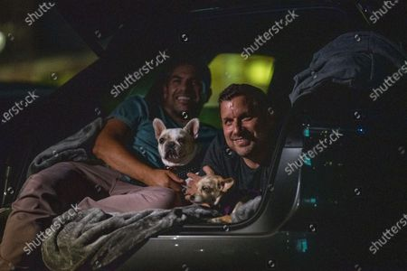 """Stock Picture of Michael Lewis, 50, and Robert Soto, 43, both of mid-city, along with their dogs Brea and Coco, watch National Lampoon's """"Vacation"""" at the Electric Dusk Drive-In atop the old Glendale Sear's parking garage on Saturday, Aug. 8, 2020 in Glendale, CA. Drive-In movies have resurged in popularity amid the coronavirus pandemic shuttering conventional movie theaters and the normal block buster hits that usually are released in the summer months. (Kent Nishimura / Los Angeles Times)"""