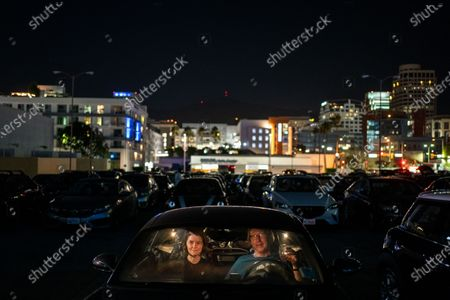 """Elsbeth Steele and Chris Williams of Cypress Park, watch National Lampoon's """"Vacation"""" at the Electric Dusk Drive-In atop the old Glendale Sear's parking garage on Saturday, Aug. 8, 2020 in Glendale, CA. Drive-In movies have resurged in popularity amid the coronavirus pandemic shuttering conventional movie theaters and the normal block buster hits that usually are released in the summer months. (Kent Nishimura / Los Angeles Times)"""