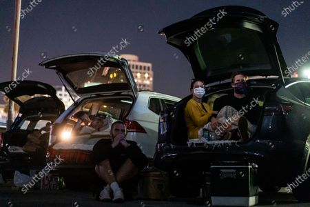 """(L to R) Cameron Cruz, Sophia Bush and Grant Hughes watch National Lampoon's """"Vacation"""" at the Electric Dusk Drive-In atop the old Glendale Sear's parking garage on Saturday, Aug. 8, 2020 in Glendale, CA. Drive-In movies have resurged in popularity amid the coronavirus pandemic shuttering conventional movie theaters and the normal block buster hits that usually are released in the summer months. (Kent Nishimura / Los Angeles Times)"""
