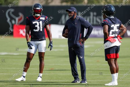 Houston Texans running backs coach Danny Barrett, center, stands with running backs David Johnson (31) and Duke Johnson (25) during an NFL training camp football practice, in Houston
