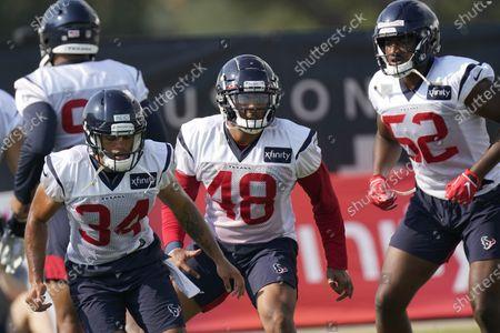 Houston Texans' John Reid (34), Nate Hall (48) and Jonathan Greenard (52) stretch during an NFL training camp football practice, in Houston