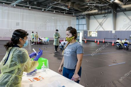 Angela Asencio, left, a LVN, explains the procedure of self-swabbing to Sade Delgado,27, at a Community COVID-19 testing site held by San Bernardino County Department of Public Health at Rancho Sports Center on Thursday, Aug. 20, 2020 in Rancho Cucamonga, CA. (Irfan Khan / Los Angeles Times)