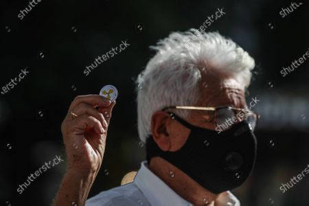 A Syrian activist holds a souvenir with a sign of the chemical weapons during a rally for the Chemical Attack on Ghota in 21 August, 2013, at Fontaine des Innocents in the Les Halles district in the 1st arrondissement of Paris, France, 21 August 2020. The rally was in the memory of the chemical attack on Eastern al-Ghouta on 21 August 2013 that killed an unconfirmed number of people that range between 281 to 1729 according to various sources, The Syrian opposition, as well as many governments, the Arab League and the European Union, stated the attack was carried out by forces of Syrian President Bashar al-Assad, as The Syrian and Russian governments blamed the opposition for the attack.