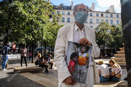 Syrians and French people demonstrate while carrying printed pictures for killed people the Chemical Attack on Ghota on 21 August 2013, at Fontaine des Innocents in the Les Halles district in the 1st arrondissement of Paris, France. 21 August 2020. The rally was in the memory of the chemical attack on Eastern al-Ghouta on 21 August 2013 that killed an unconfirmed number of people that range between 281 to 1729 according to various sources, The Syrian opposition, as well as many governments, the Arab League and the European Union, stated the attack was carried out by forces of Syrian President Bashar al-Assad, as The Syrian and Russian governments blamed the opposition for the attack.