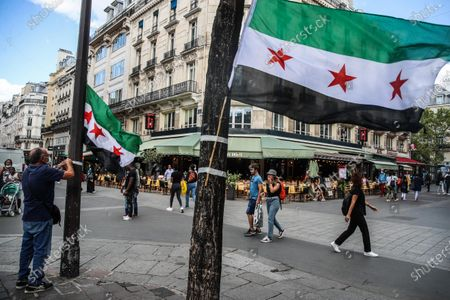 A Syrian activist hangs the Syrian Revolution flage during a rally for the Chemical Attack on Ghota in 21 August, 2013, at Fontaine des Innocents in the Les Halles district in the 1st arrondissement of Paris, France. 21 August 2020. The rally was in the memory of the chemical attack on Eastern al-Ghouta on 21 August 2013 that killed an unconfirmed number of people that range between 281 to 1729 according to various sources, The Syrian opposition, as well as many governments, the Arab League and the European Union, stated the attack was carried out by forces of Syrian President Bashar al-Assad, as The Syrian and Russian governments blamed the opposition for the attack.
