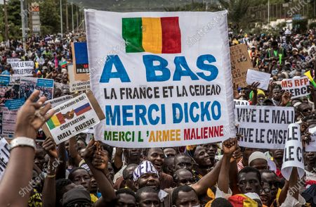 """Malians supporting the recent overthrow of President Ibrahim Boubacar Keita gather to celebrate in the capital Bamako, Mali . Hundreds marched in the streets of Mali's capital Friday to celebrate the overthrow of Keita, as the West African country's longtime political opposition backed the military's junta plan to eventually hand over power to a civilian transitional government. Main banner in French reads """"Down with France and ECOWAS, Thank you Dicko, Thank you to the Malian Army"""" referring to Mahmoud Dicko, an imam who has helped lead the movement against Keita"""