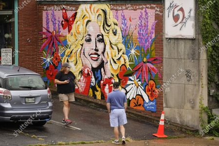 People look at a mural of Dolly Parton outside The 5 Spot, a music club in Nashville, Tenn., . Artist Kim Radford said Dolly fans from around the world have contacted her about the mural, which contains a quote from Parton about her support for the Black Lives Matter movement