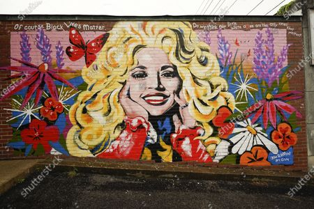 Mural of Dolly Parton is seen outside The 5 Spot, a music club in Nashville, Tenn., . Artist Kim Radford said Dolly fans from around the world have contacted her about the mural, which contains a quote from Parton about her support for the Black Lives Matter movement