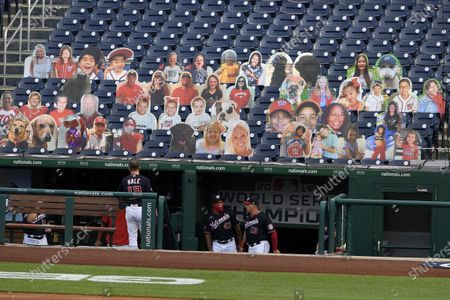 Washington Nationals' Howie Kendrick (47) and Asdrubal Cabrera (13) walk up the dugout steps as cutouts in the stands are displayed before a baseball game against the Miami Marlins, in Washington