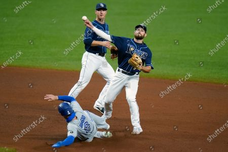 Stock Image of Tampa Bay Rays second baseman Brandon Lowe forces Toronto Blue Jays' Cavan Biggio (8) at second base and relays the throw to first in time to turn a double play on Santiago Espinal during the fourth inning of a baseball game, in St. Petersburg, Fla. Backing up the play is shortstop Joey Wendle