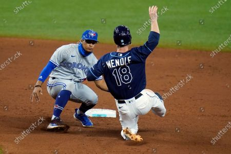 Toronto Blue Jays shortstop Santiago Espinal tags out Tampa Bay Rays' Joey Wendle (18) attempting to steal second base during the eighth inning of a baseball game, in St. Petersburg, Fla