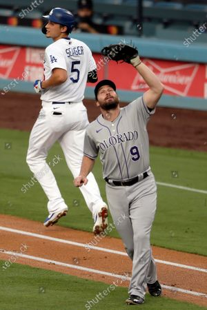 Colorado Rockies first baseman Daniel Murphy, right, catches an infield fly ball hit by Los Angeles Dodgers' Corey Seager (5) during the first inning of a baseball game in Los Angeles