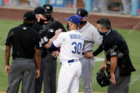 Umpire Bill Miller (26) gives out instructions to Los Angeles Dodgers manager Dave Roberts (30) and Colorado Rockies manager Bud Black, second from right, before a baseball game in Los Angeles