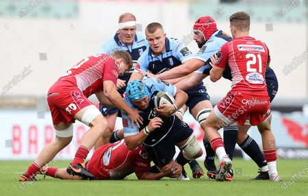 Olly Robinson of Cardiff Blues is tackled by Josh Macleod and James Davies of Scarlets.