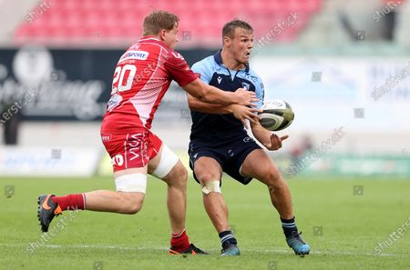 Jarrod Evans of Cardiff Blues is challenged by James Davies of Scarlets.