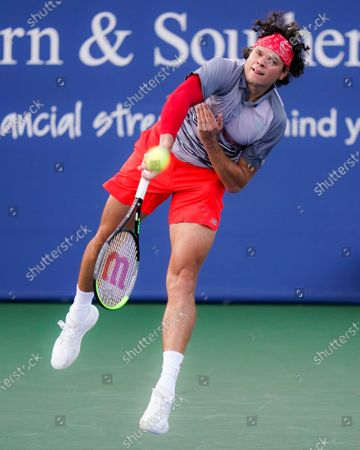 Milos Raonic, of Canada, serves to Sam Querrey, of the United States, at the Western & Southern Open tennis tournament, in New York
