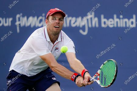 Sam Querrey, of the United States, returns to Milos Raonic, of Canada, at the Western & Southern Open tennis tournament, in New York