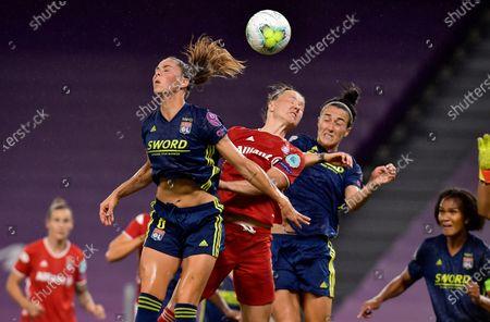 Lyon's Sara Bjork Gunnarsdottir, left, and Lucy Bronze challenge Bayern's Marina Hegering, center, during the Women's Champions League quarterfinal soccer match between Lyon and Bayern Munich in Bilbao, Spain