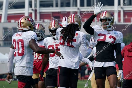 San Francisco 49ers' Jimmie Ward (20) and Richard Sherman, center, greet Ahkello Witherspoon, right, during NFL football practice in Santa Clara, Calif