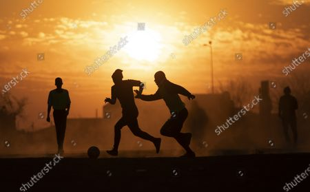 People play soccer in a dusty field in Soweto, South Africa, . South African president Cyril Ramaphosa announced that the entire country move to lockdown alert level 2 from Tuesday