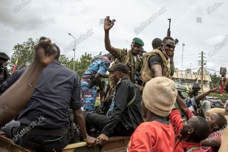 People cheer in celebration as security forces drive through the streets of the capital Bamako, Mali, a day after armed soldiers fired into the air outside President Ibrahim Boubacar Keita's home and took him into their custody. African and Western leaders condemned on Wednesday the junta that forced Mali's president from power, warning the coup was a deep setback for the West African nation that could threaten the battle against Islamic extremism