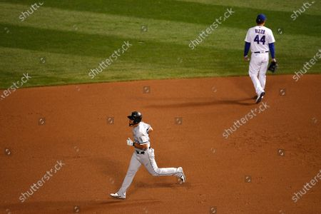 Chicago White Sox's Jose Abreu, left, rounds the bases past Chicago Cubs first baseman Anthony Rizzo (44) after hitting a home run during the ninth inning of a baseball game, in Chicago