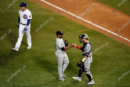 Chicago White Sox relief pitcher Alex Colome, center, celebrates with catcher Yasmani Grandal, right, after defeating the Chicago Cubs as Cubs' Anthony Rizzo walks off the field after a baseball game, in Chicago
