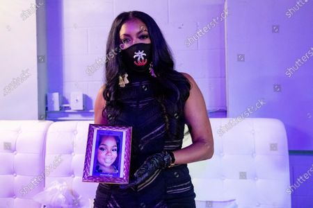 Actress Porsha Williams poses for a photo with a framed picture of Breonna Taylor at the Taylor-Made Women's Empowerment Event at Vibes presented by Until Freedom on Day 1 of BreonnaCon, in Louisville, Ky